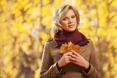 Jeune femme blonde heureuse de mode dans la marche beige classique de manteau extérieure images libres de droits