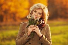 Jeune femme blonde heureuse de mode portant la marche beige classique de manteau extérieure photos stock