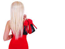 Jeune femme blonde jugeant les chaussures rouges sexy de talon haut d'isolement Photographie stock libre de droits