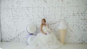 Jeune femme blonde mignonne dans la robe de mariage avec le bouquet de fleurs posant dans le studio sur la crème glacée et les ma banque de vidéos