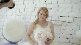 Jeune femme blonde mignonne dans la robe de mariage avec le bouquet de fleurs posant pour le photographe dans le studio sur la gl banque de vidéos