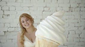 Jeune femme blonde mignonne dans la robe de mariage posant dans le studio avec la crème glacée énorme clips vidéos