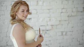 Jeune femme blonde mignonne dans la robe de mariage posant dans le studio avec la sucrerie banque de vidéos