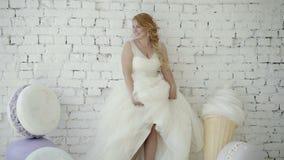 Jeune femme blonde mignonne dans la robe de mariage posant et dansant dans le studio sur la crème glacée et les macaronis énormes clips vidéos