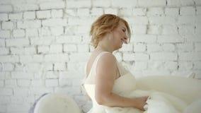 Jeune femme blonde mignonne dans la robe de mariage posant et dansant dans le studio sur la crème glacée et les macaronis énormes banque de vidéos