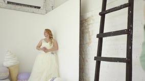 Jeune femme blonde mignonne dans la robe de mariage posant pour le photographe dans le steadicam de studio banque de vidéos
