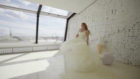 Jeune femme blonde mignonne dans la robe de mariage posant pour le photographe le studio et en entourant clips vidéos