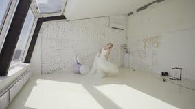 Jeune femme blonde mignonne dans la robe de mariage posant pour le photographe le studio et en entourant banque de vidéos