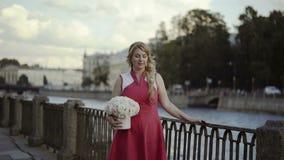 Jeune femme blonde mignonne dans la robe rouge marchant dans la rue avec des fleurs banque de vidéos
