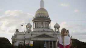 Jeune femme blonde mignonne dans la robe rouge regardant la cathédrale banque de vidéos