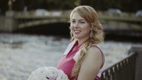 Jeune femme blonde mignonne dans la robe rouge restant sur le remblai clips vidéos