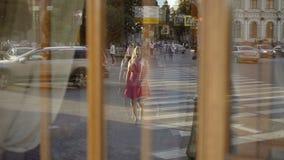 Jeune femme blonde mignonne dans la route rouge de croisement de robe par réflexion clips vidéos