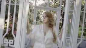 Jeune femme blonde mignonne dans le defocus en verre ouvert de portes de lingerie clips vidéos