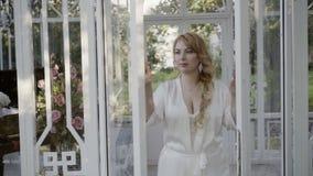 Jeune femme blonde mignonne dans les portes en verre ouvertes de lingerie clips vidéos