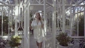 Jeune femme blonde mignonne dans les portes en verre ouvertes de lingerie banque de vidéos