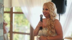 Jeune femme blonde parlant dans le microphone banque de vidéos