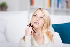 Jeune femme blonde pensant avec des verres photo libre de droits