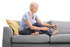 Jeune femme blonde polissant ses ongles de pied Image libre de droits