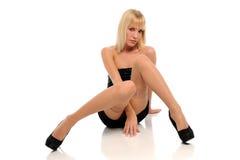 Jeune femme blonde portant une robe noire courte Photos libres de droits