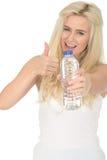 Jeune femme blonde positive en bonne santé convenable tenant une bouteille de l'eau minérale Image libre de droits