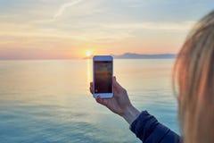 Jeune femme blonde prenant une photo d'un coucher du soleil coloré d'océan photographie stock libre de droits