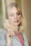 Jeune femme blonde réfléchie avec les yeux perdus de la fenêtre Image libre de droits