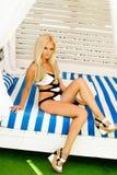 Jeune femme blonde s'asseyant dans le maillot de bain Image stock