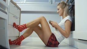 Jeune femme blonde s'asseyant dans un plancher de cuisine et dactylographiant au téléphone portable clips vidéos