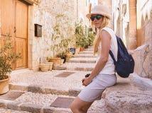 Jeune femme blonde s'asseyant sur la rue photos stock