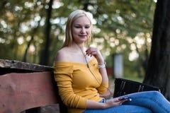 Jeune femme blonde s'asseyant sur un banc en bois en parc, écoutant la musique Photos stock
