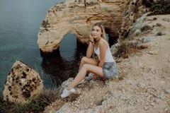 Jeune femme blonde s'asseyant sur une falaise et apprécier la vue de l'océan et de la plage dans l'heure d'été près de l'Océan At photographie stock