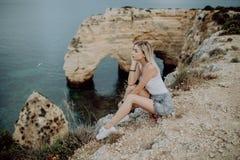 Jeune femme blonde s'asseyant sur une falaise et apprécier la vue de l'océan et de la plage dans l'heure d'été près de l'Océan At photos stock
