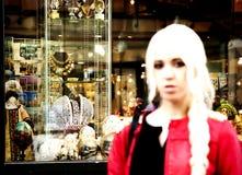 Jeune femme blonde se tenant à côté d'une boutique de souvenirs sur la vieille AR Photo stock