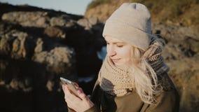 Jeune femme blonde se tenant dans l'endroit de montagnes et prenant la photo de selfie sur le smartphone sur le beau fond banque de vidéos