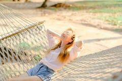 Jeune femme blonde se trouvant sur l'hamac en osier blanc avec le sable à l'arrière-plan Photos stock