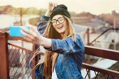 Jeune femme blonde sexy de hippie posant pour le selfie et rire Jeans de port veste, chapeau noir de hippie et verres lifestyle images stock