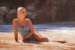 Jeune femme blonde sexy et décontractée dans le maillot de bain d'une seule pièce se trouvant sur le sable regardant la mer appré photographie stock libre de droits