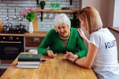 Jeune femme blonde soulageant la femme aux cheveux gris bouleversée avec du charme pendant les années image stock