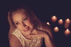 Jeune femme blonde sur les feuilles noires avec des candels à l'arrière-plan Image libre de droits