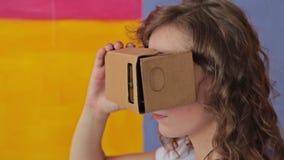 Jeune femme bouclée employant des verres de réalité virtuelle