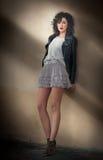 Jeune femme bouclée avec du charme de brune dans la jupe courte de dentelle et la veste en cuir noire se penchant contre un mur J Photographie stock