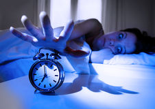 Jeune femme bouleversée de choc à la maison dans le lit ne voulant pas se réveiller arrêtant son réveil Images libres de droits
