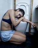 Jeune femme boulimique triste et déprimée sentant la séance en difficulté au plancher de la toilette se penchant sur la carte de  Photo libre de droits