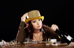 Jeune femme bue avec la bouteille vide de champagne Images stock