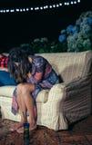 Jeune femme bue s'asseyant dans le sofa sur une partie Photo libre de droits