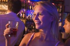 Jeune femme buvant à une boîte de nuit Photos libres de droits