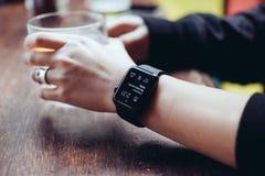 Jeune femme buvant avec la montre intelligente à la barre photographie stock