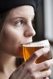 Jeune femme buvant de la bière blanche d'Inda Photographie stock libre de droits