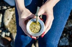 Jeune femme buvant du thé argentin traditionnel de compagnon de yerba de la courge de calebasse photo stock