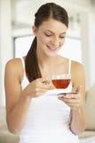 Jeune femme buvant du thé de fines herbes Photos libres de droits